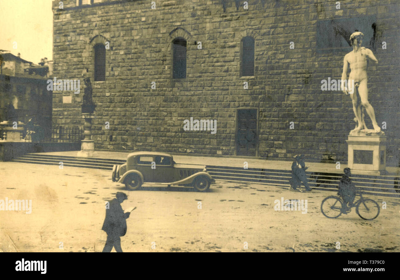 People, car, and bicycle in Piazza della Signoria, Florence, Italy 1930s - Stock Image