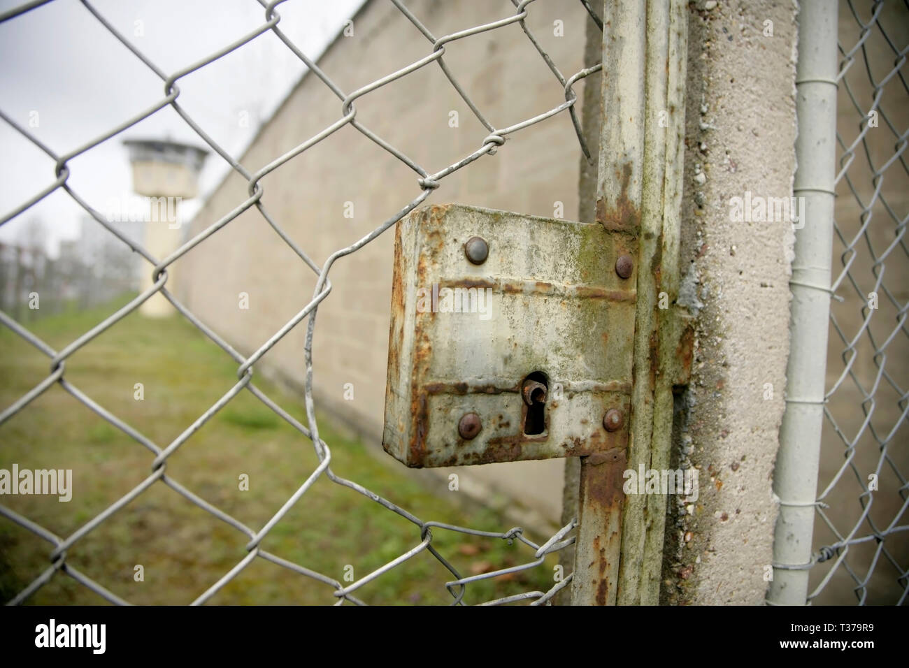 Locked gate in chain link fence, and watchtower in the perimeter of the Stasi HQ Hohenschonhausen complex, Berlin, Germany. - Stock Image