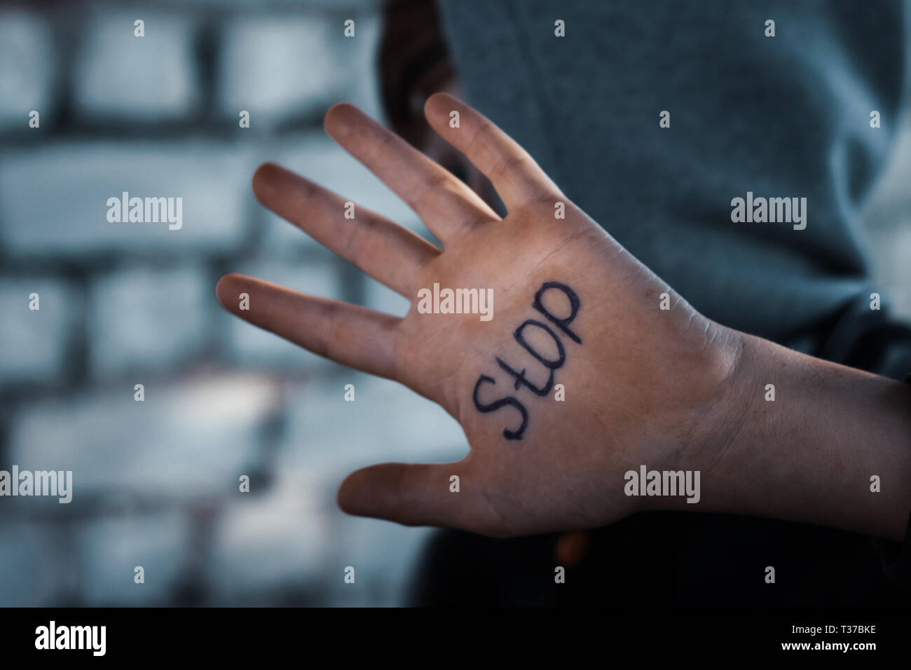 the boy closes his hand, written on his hand stop, cruelty to children Stock Photo