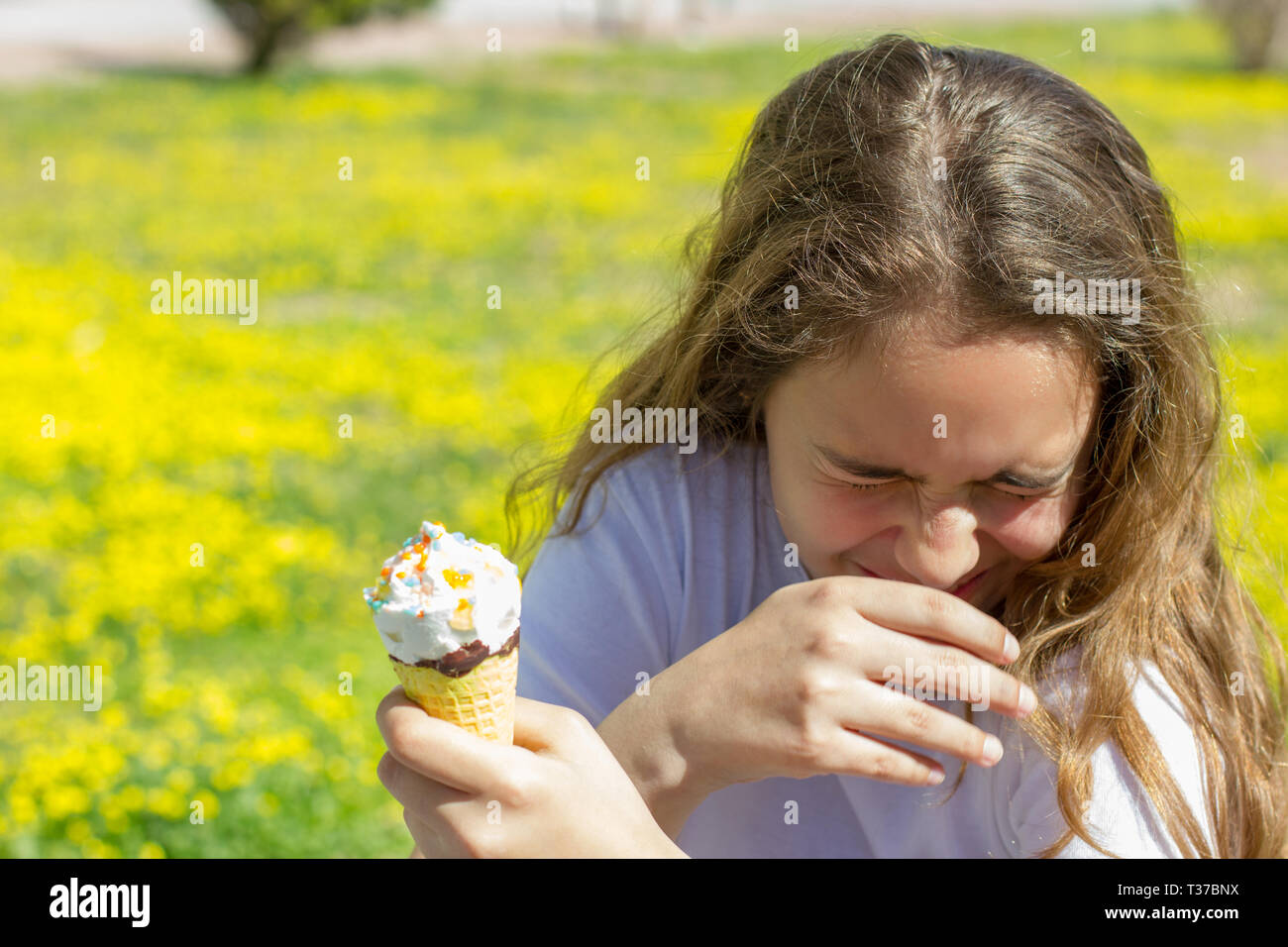 Dissatisfied unhappy teen girl eats tasteless ice cream in waffle cone in summer - Stock Image