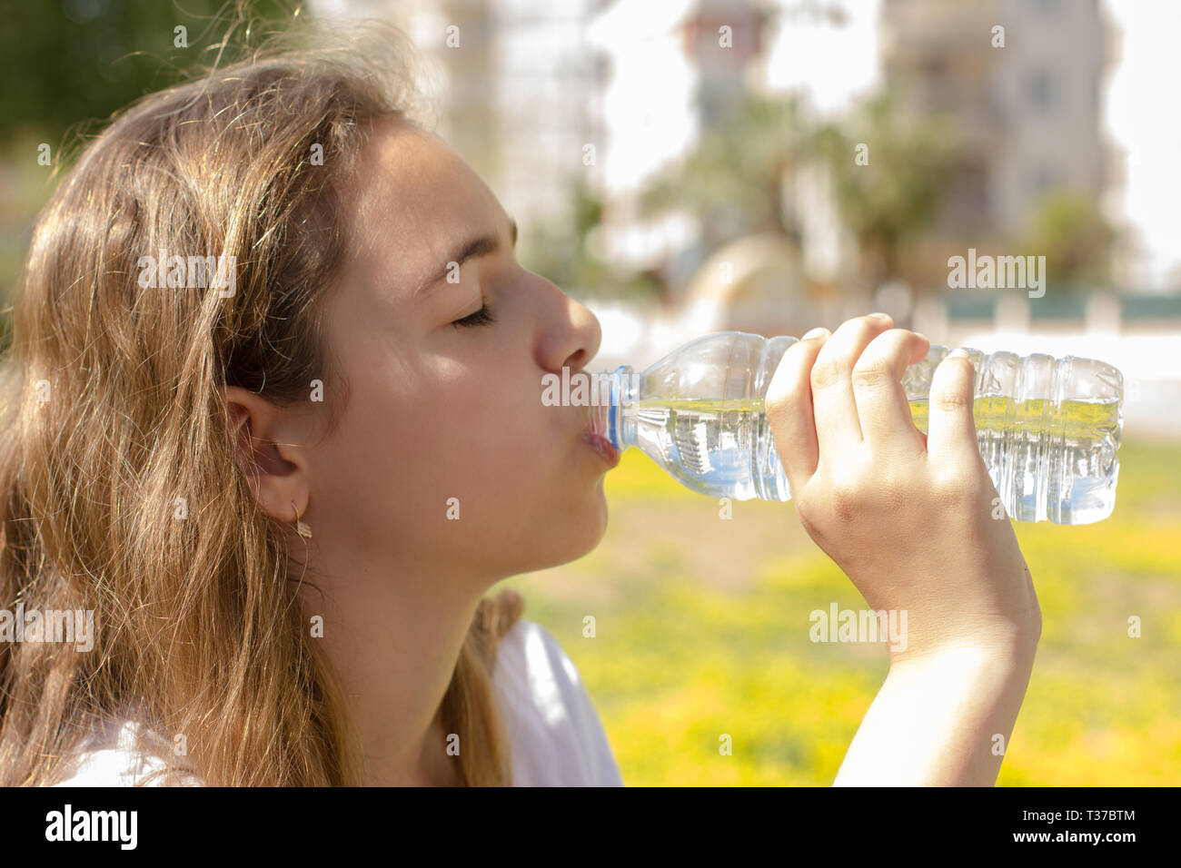 Beautiful teen girl drinks clean water from a plastic bottle on hot summer day - Stock Image