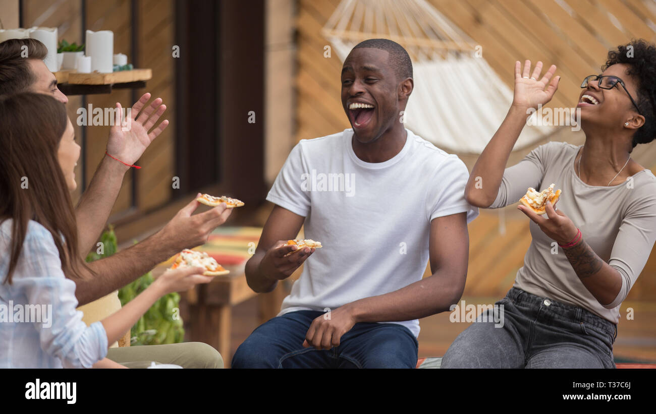 Happy diverse friends talking laughing sharing dinner in cafe Stock Photo