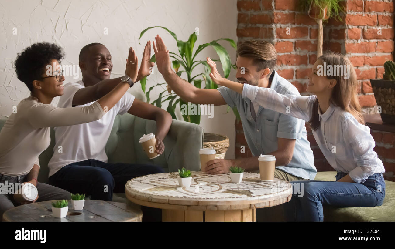 Happy multicultural friends  group giving high five at coffeehouse meeting - Stock Image