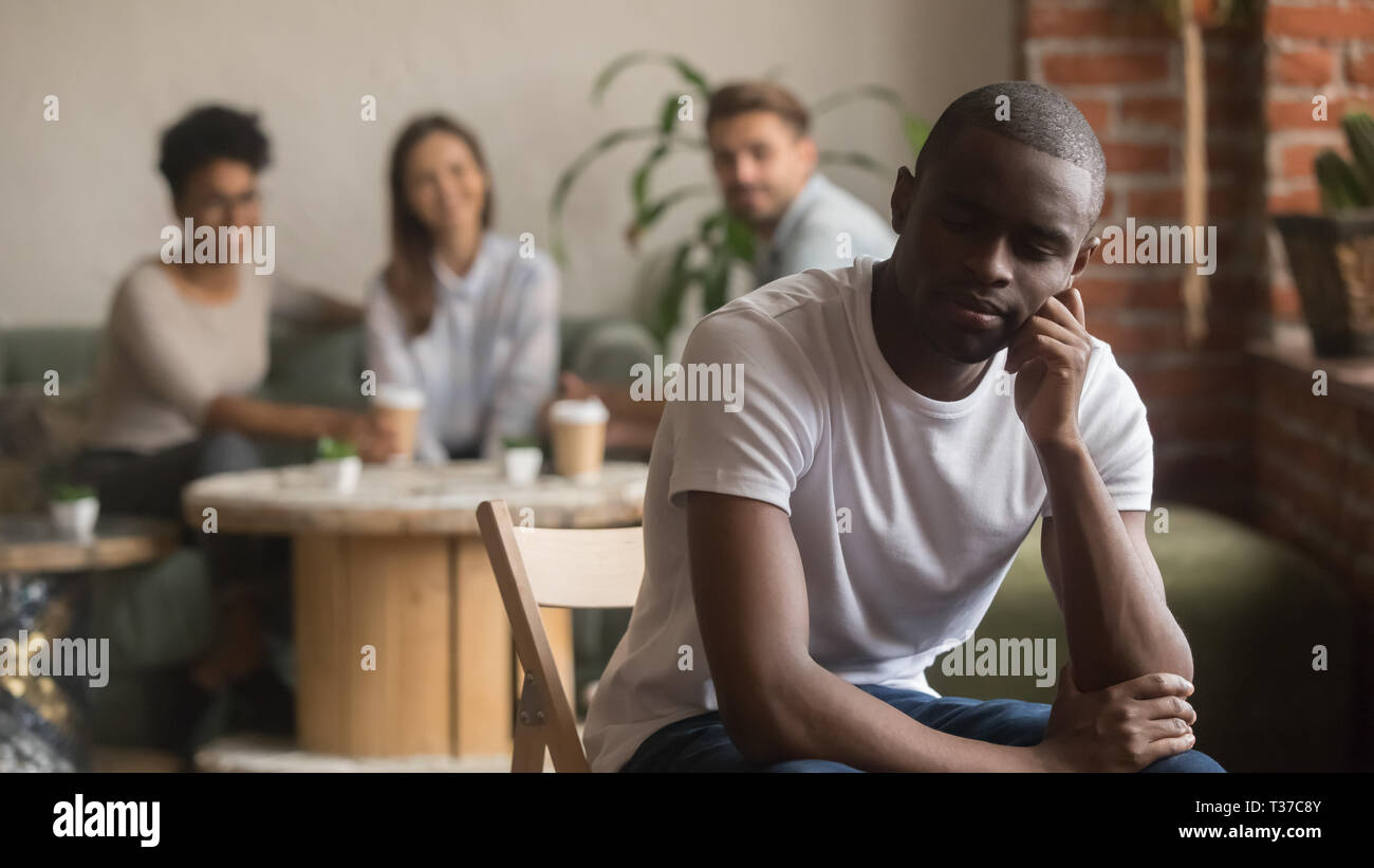 Upset lonely african american man suffering from bullying racial discrimination - Stock Image