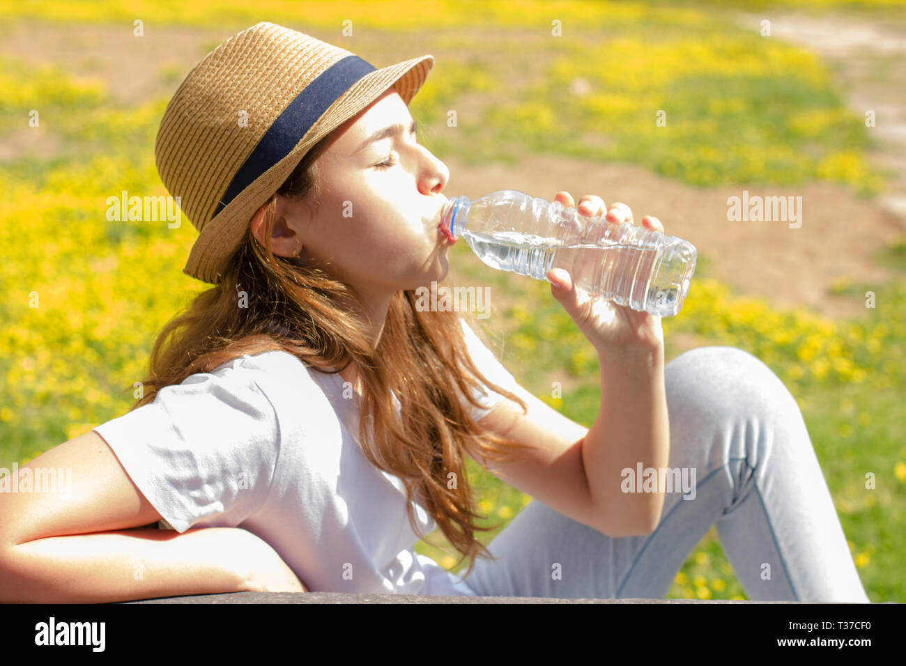 Beautiful teen girl drinks clean water from a plastic bottle on hot summer day. Selective focus - Stock Image