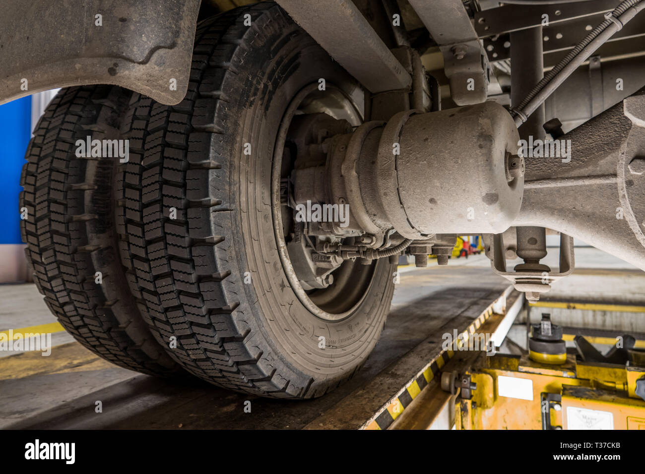 View of disc brakes and suspension on a small truck from maintenance pit. - Stock Image