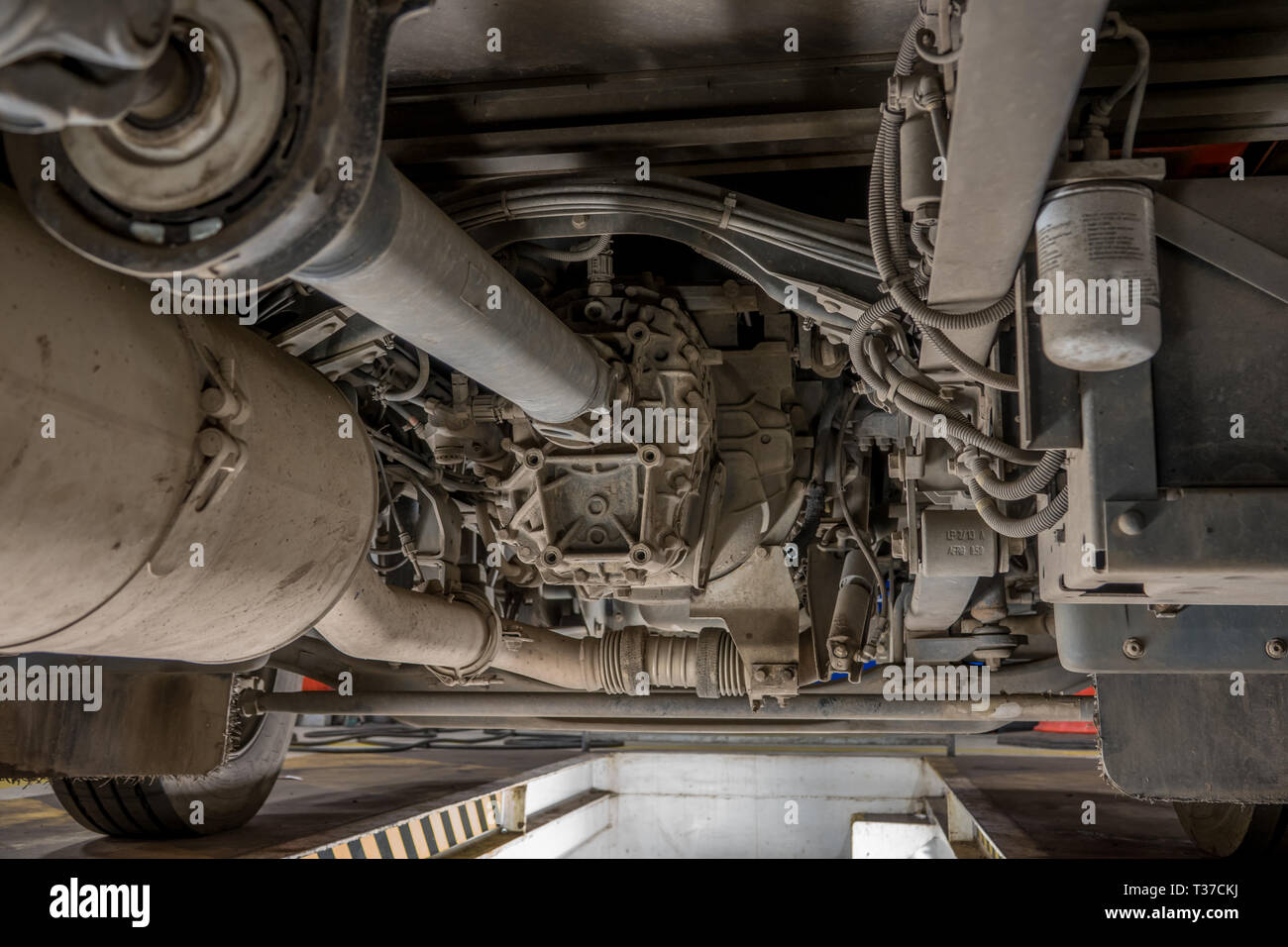 View of front axle and gearbox of a small truck from a maintenance pit. - Stock Image