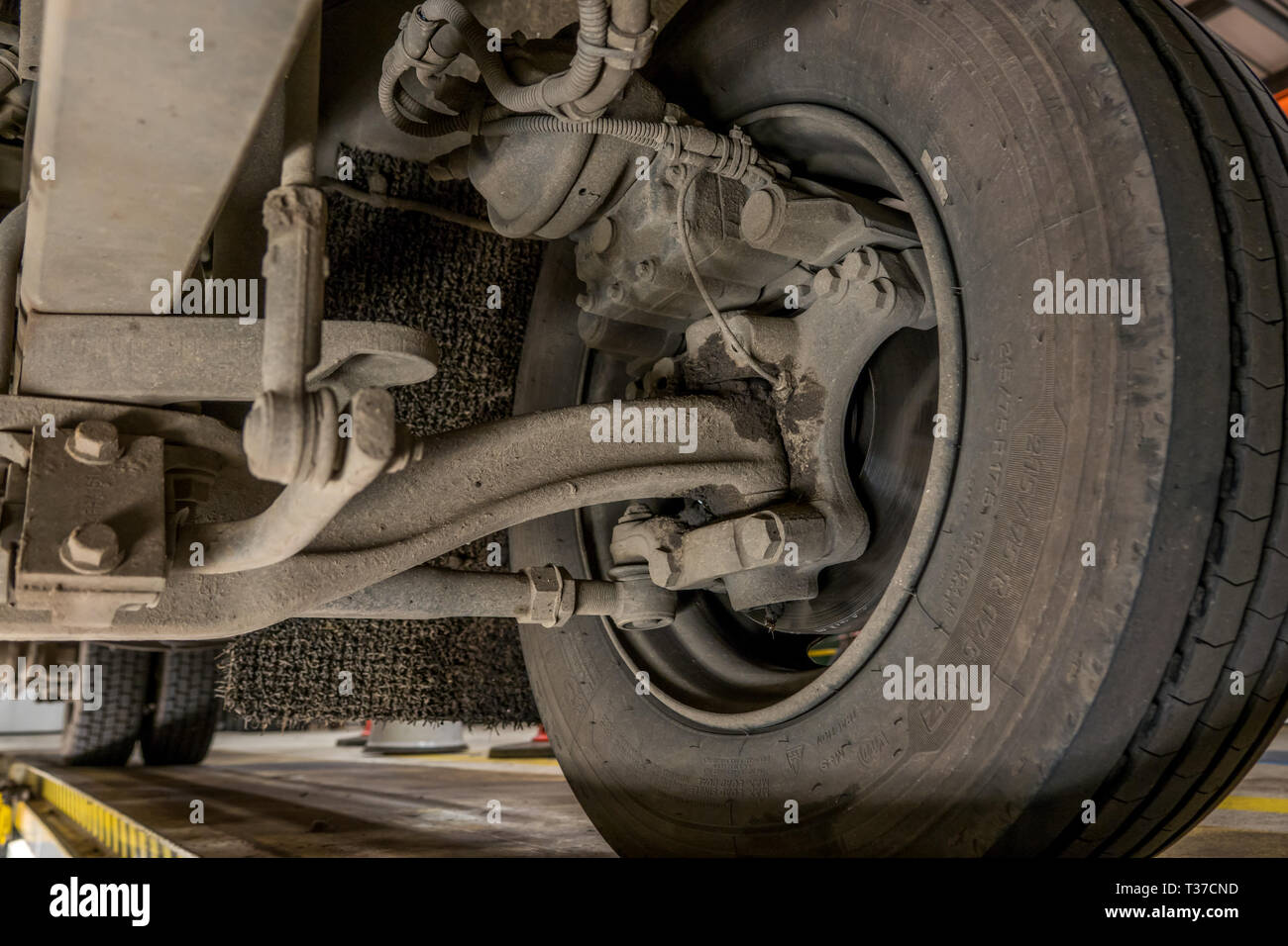 View of disc brakes,suspension and steering joints on a small truck from maintenance pit. - Stock Image