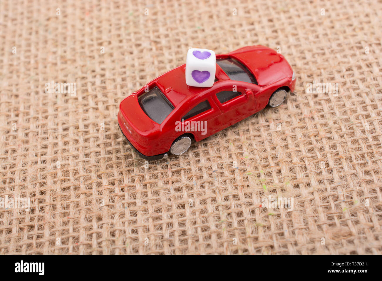 Love cube on a red toy car on a linen canvas - Stock Image