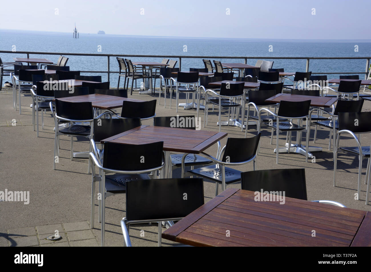 tables and chairs without persons on the lakeside promenade against lake constance and ferry and bouys at the horizon, empty restaurant in early sprin Stock Photo