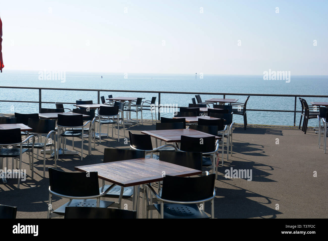 empty cafe in early spring at lake constance in germany, tables and chairs without persons on the lakeside promenade against lake constance and bouys  Stock Photo