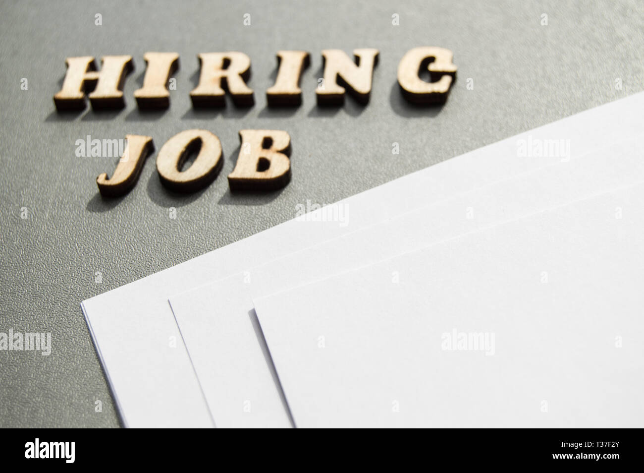 Hiring JOB is written in wooden letters on a gray background, near white sheets of paper, layout for design, ad layout, hiring concept. - Stock Image