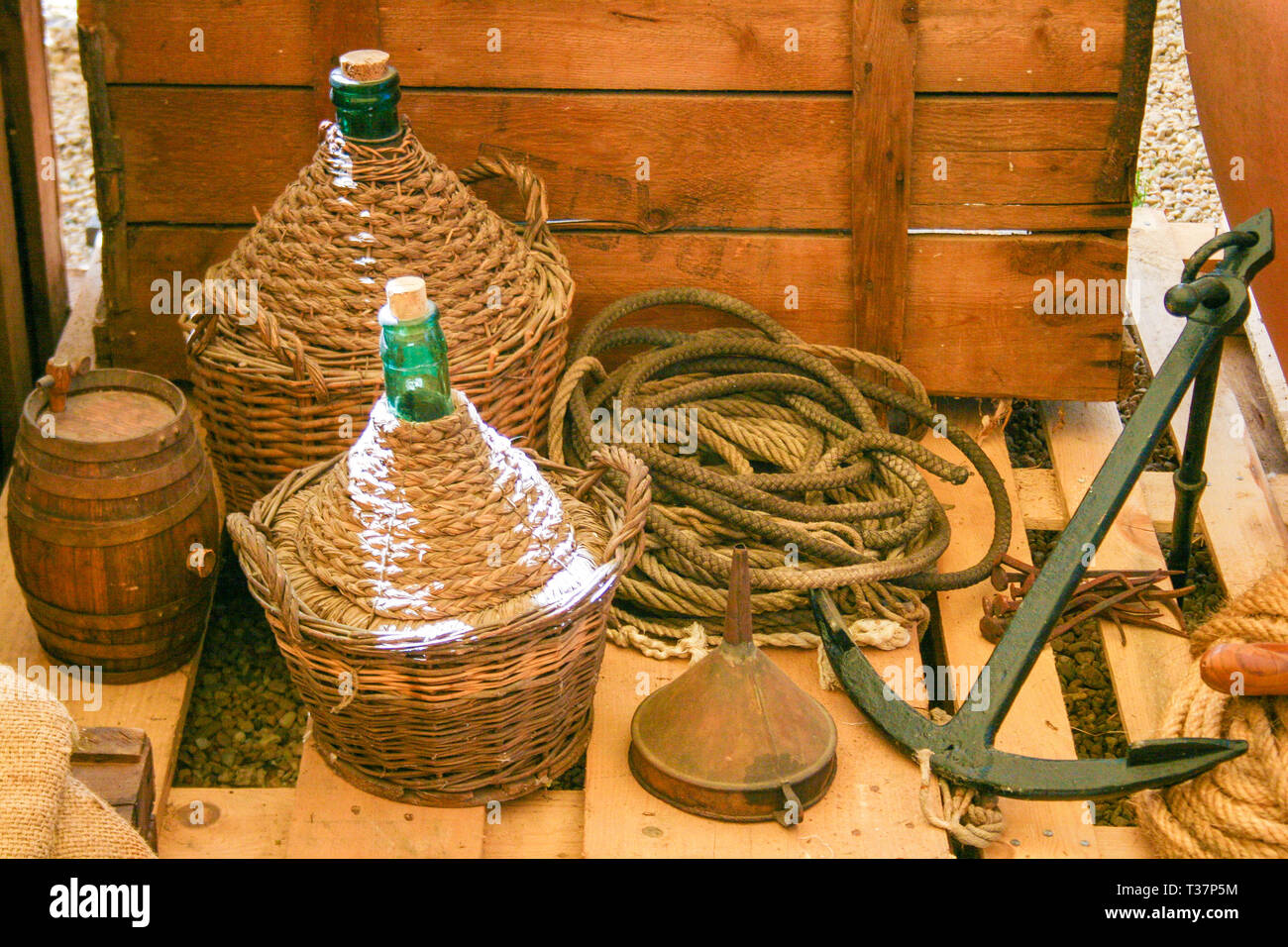 Composition with old wooden cart and wine flasks with old rope and anchor in Italy - Stock Image