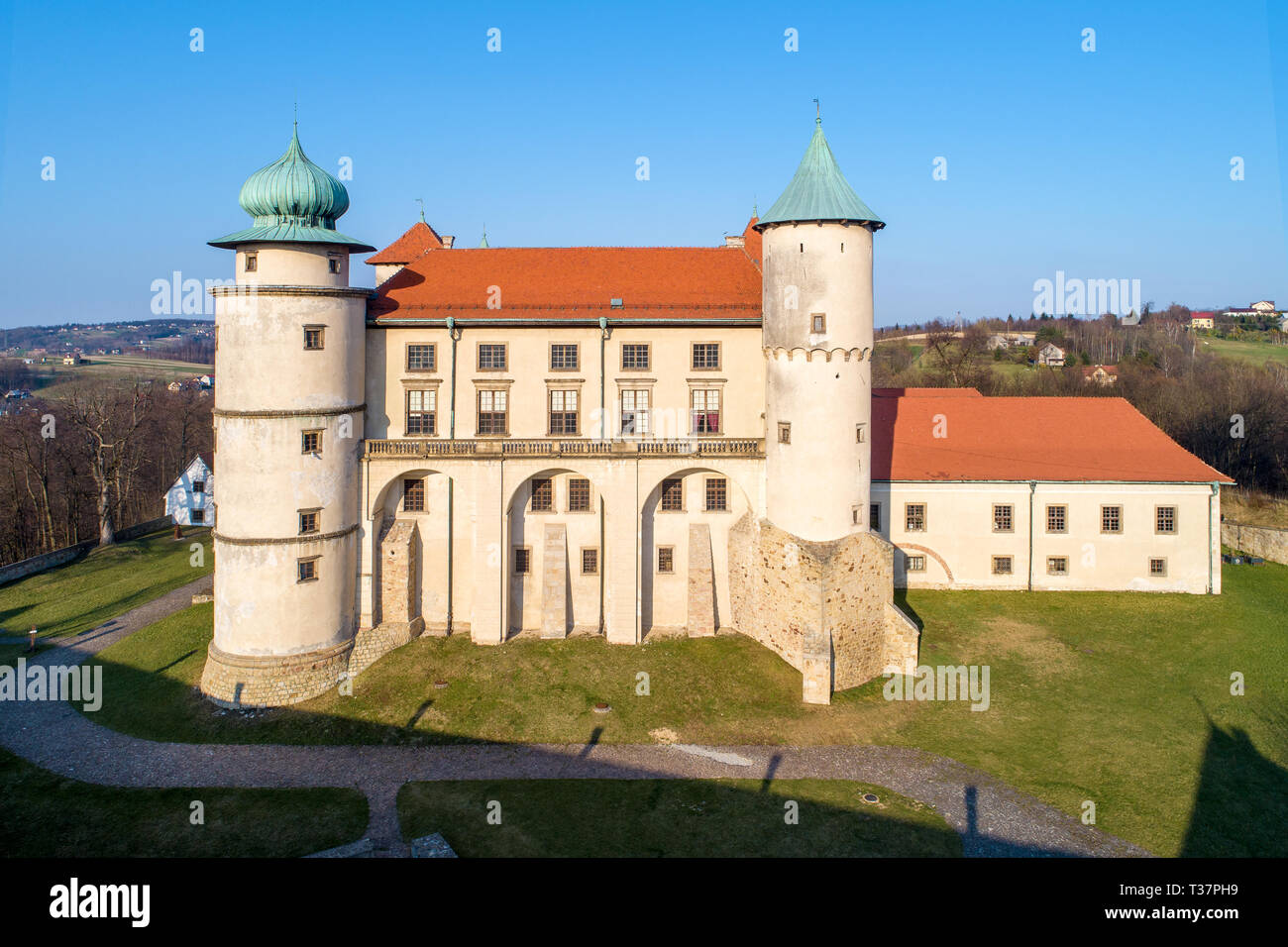 Poland. Renaissance, partly Baroque Castle on the hill in Nowy WiÅ›nicz. Presently owned by Polish state. Aerial view in spring. Sunset light. - Stock Image