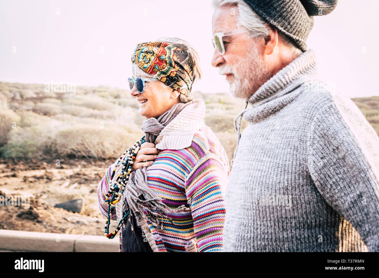 Aged coloured happy fashion hippy couple senior people in outdoor leisure activity together in couple - cold season and cheerful woman with husband in Stock Photo