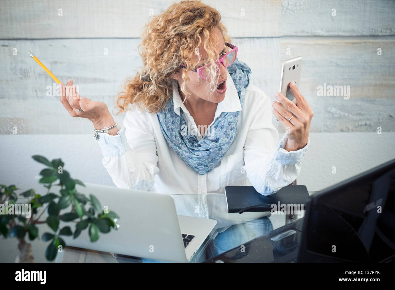 Stressed business woman shout at the phone call - two laptop on the desk and technology everywhere to work - workstation with female people - modern j Stock Photo