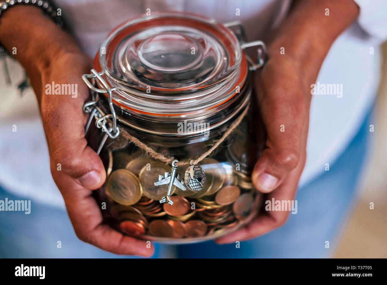 Middle age caucasian woman show her income to travel for the next vacation or adventure - european euro coin in a glass vase - home economy concept fo Stock Photo