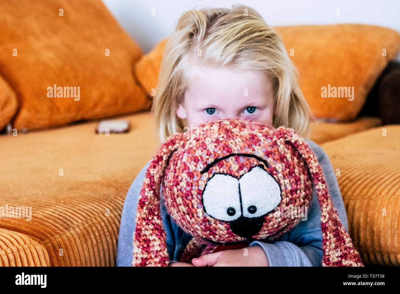 Young playful blonde caucasian children play with puppy at home - childhood lifestyle and colors in background Stock Photo