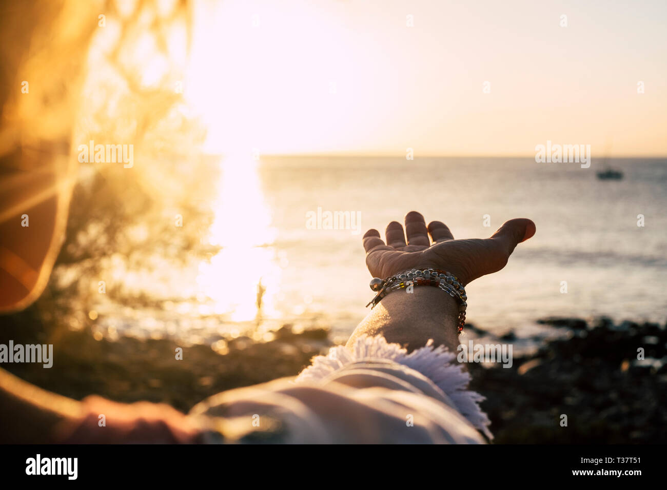 Sunset sunlight folden colors and ocean in background- woman with accessories with and to take the quiet sea - vacation and travel concept for wanderl Stock Photo