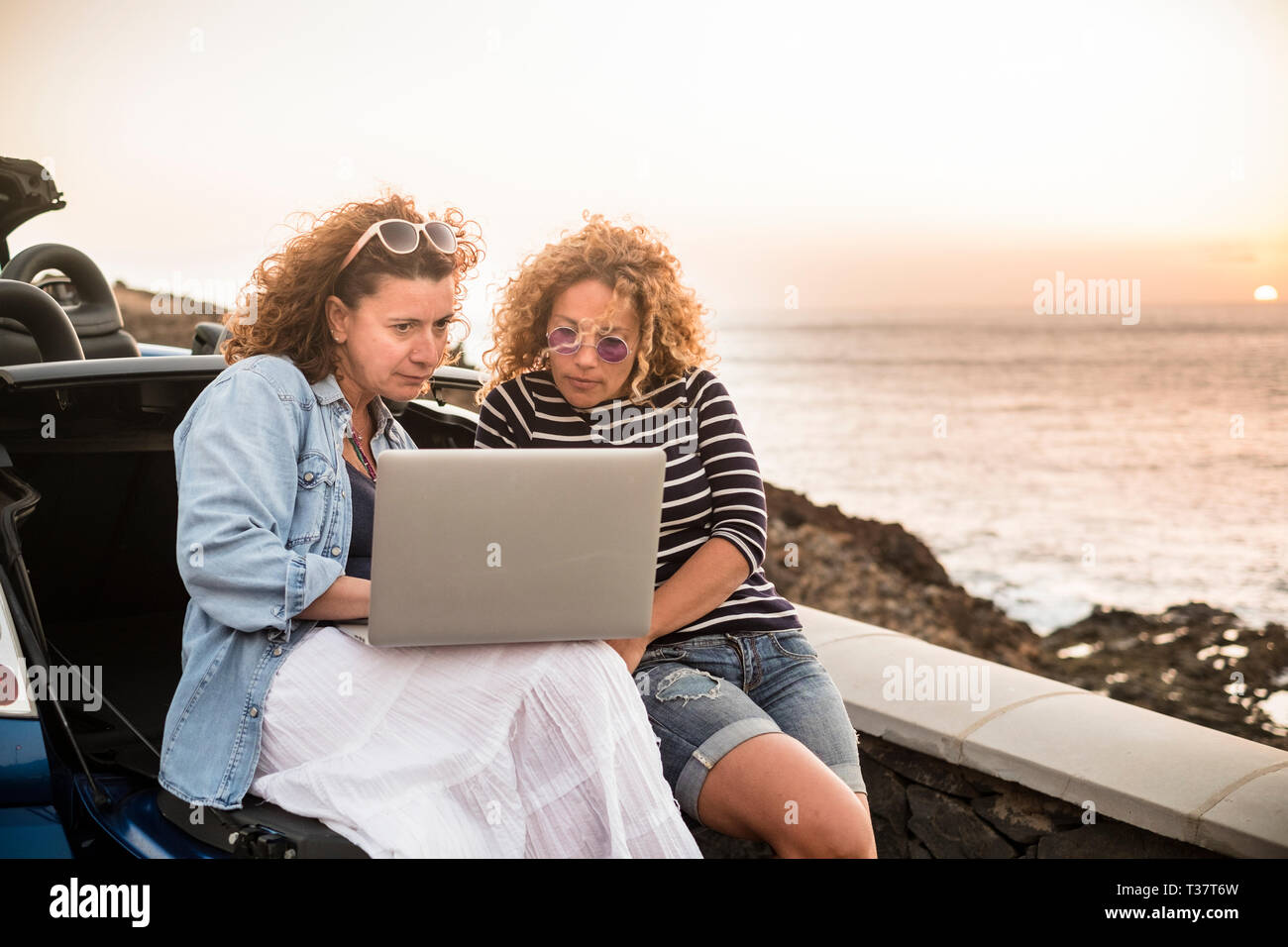 Couple of people women friends use together a laptop computer sitting on the back of convertible car and sunset on the ocean in background - work ever Stock Photo