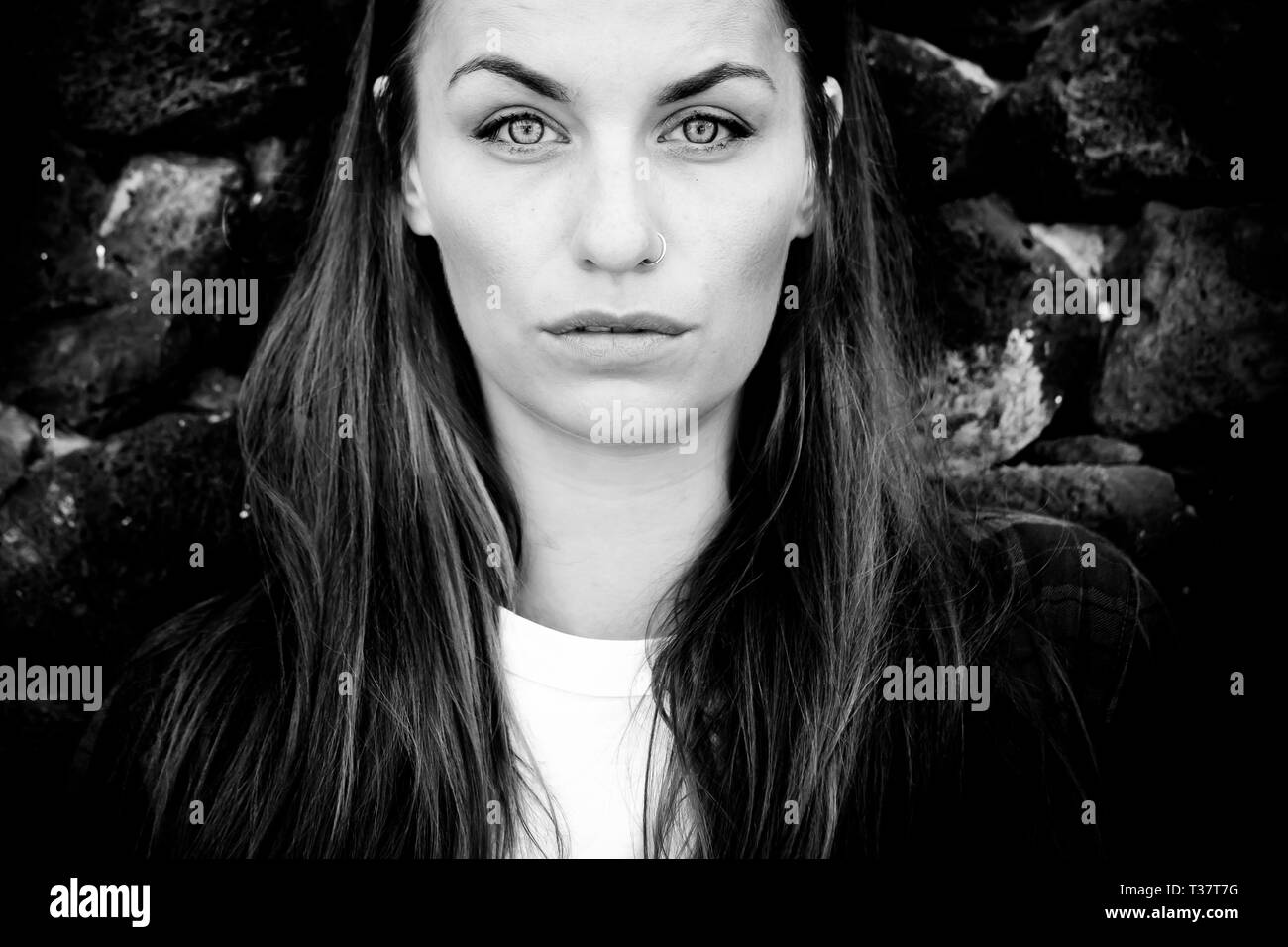 Black and white beautiful caucasian young woman portrait with clear blue eyes and serious expression Stock Photo