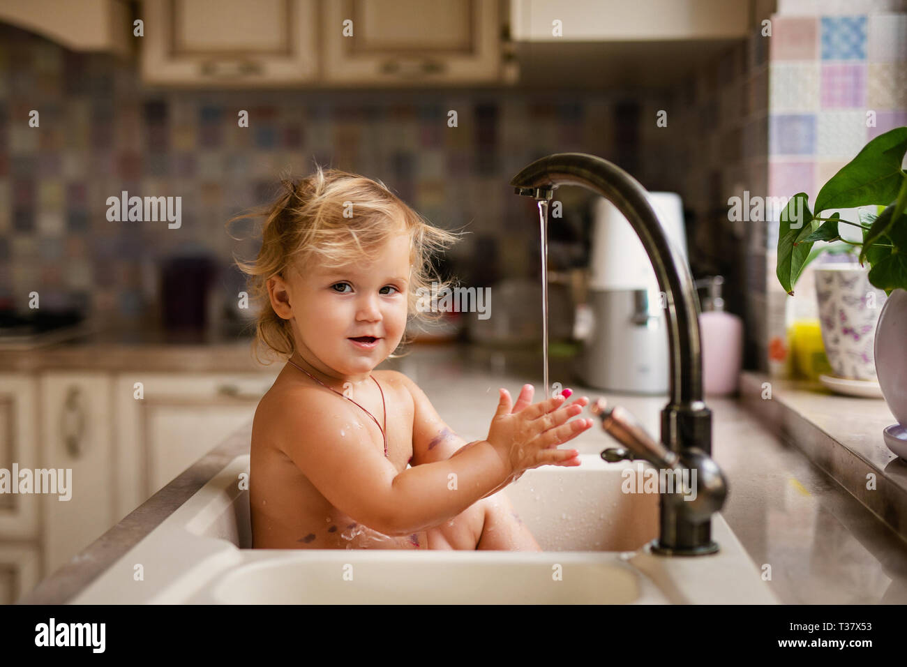 Baby Taking Bath In The Kitchen Sink Child Playing With Water And Soap Bubbles In A Sunny Kitchen With Window Water Fun For Kids Hygiene And Skin Care Fo Stock Photo