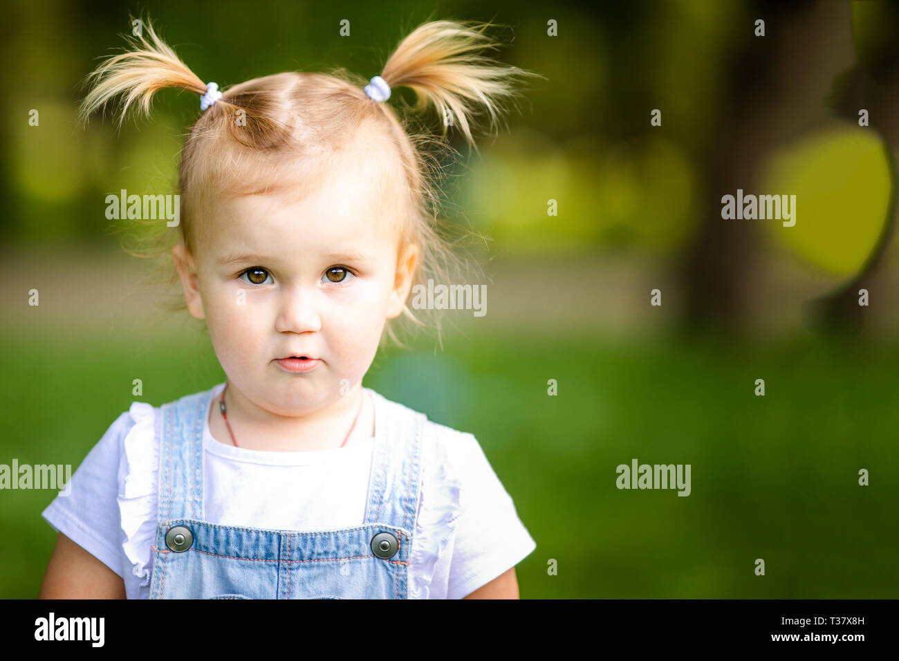 4d7bef651c Happy funny blonde baby girl with two little braids in white t-shirt and  jeans