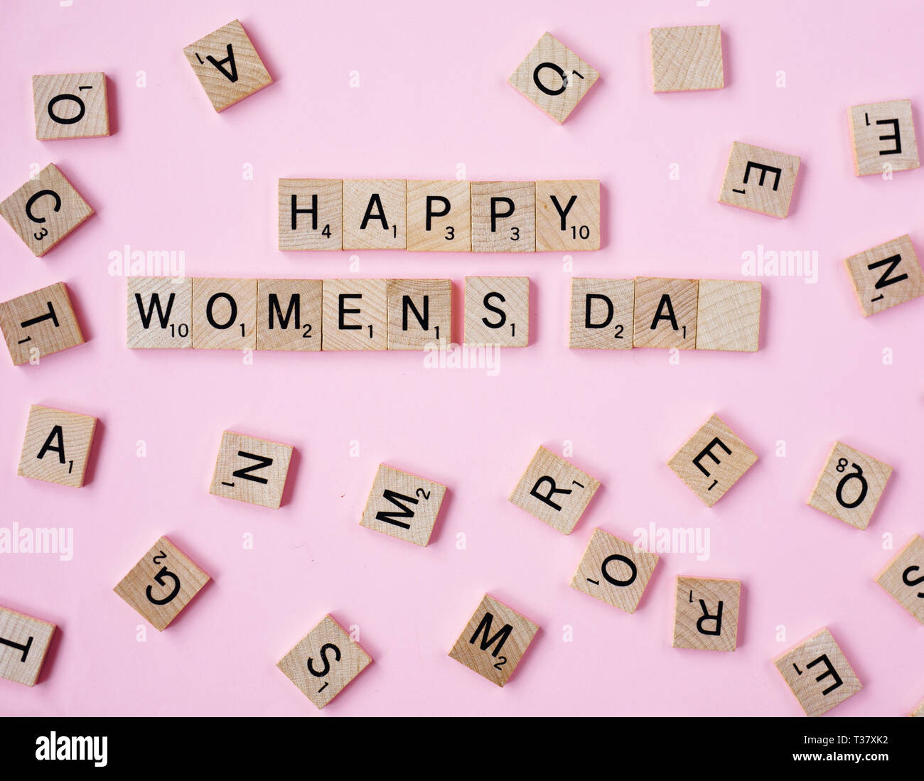 Top view Message happy woomans day spelled in wooden blocks on pink background. Love, 8 march background. Gift, greeting, compliment concept. Copy spa Stock Photo