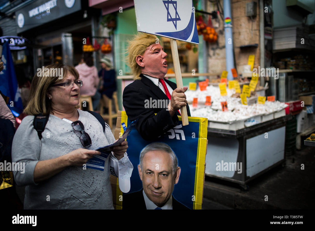 Jerusalem, Middle East. 7th Apr, 2019. A supporter of the Likud party, is seen dressed as US President Donald Trump, as he walks in the Mahane Yehuda Market with a picture of Israeli Prime Minister Benjamin Netanyahu, ahead of the Israeli general elections that is scheduled to take place on 09 April. Credit: Ilia Yefimovich/dpa/Alamy Live News - Stock Image