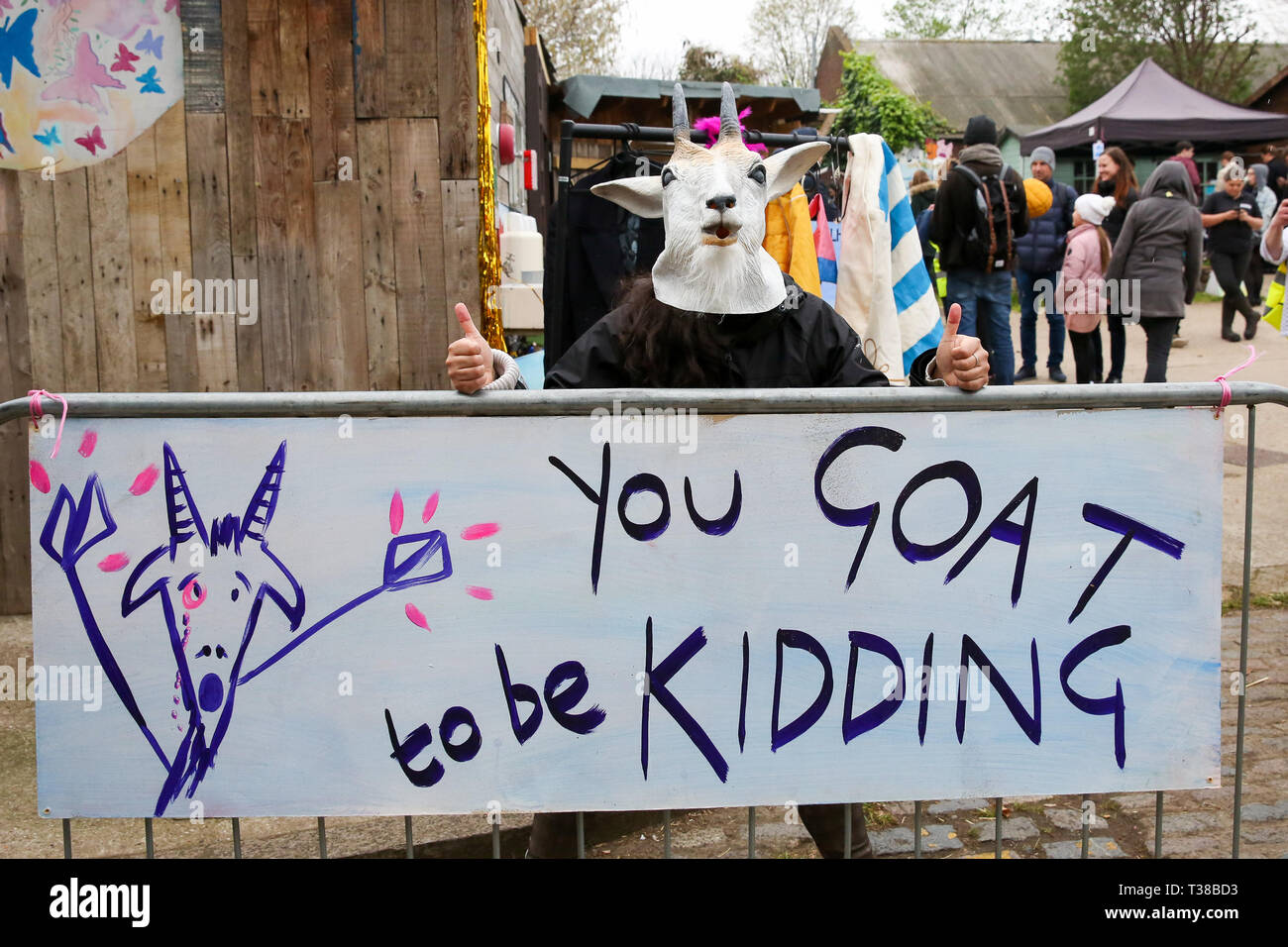 London, UK, UK. 7th Apr, 2019. A man seen wearing a goat horns face mask while holding a banner that says you goat to be kidding before the Oxford vs Cambridge Goat Race in East London.Two pygmy goats compete during the 10th Oxford and Cambridge Goat Race at Spitalfields City Farm, Bethnal Green in East London. The annual fundraising event, which takes place at the same time as the Oxford and Cambridge boat race, where two goats, one named Hamish representing Oxford and the other Hugo representing Cambridge to be crowned King Billy. (Credit Image: © Dinendra Haria/SOPA Images vi - Stock Image