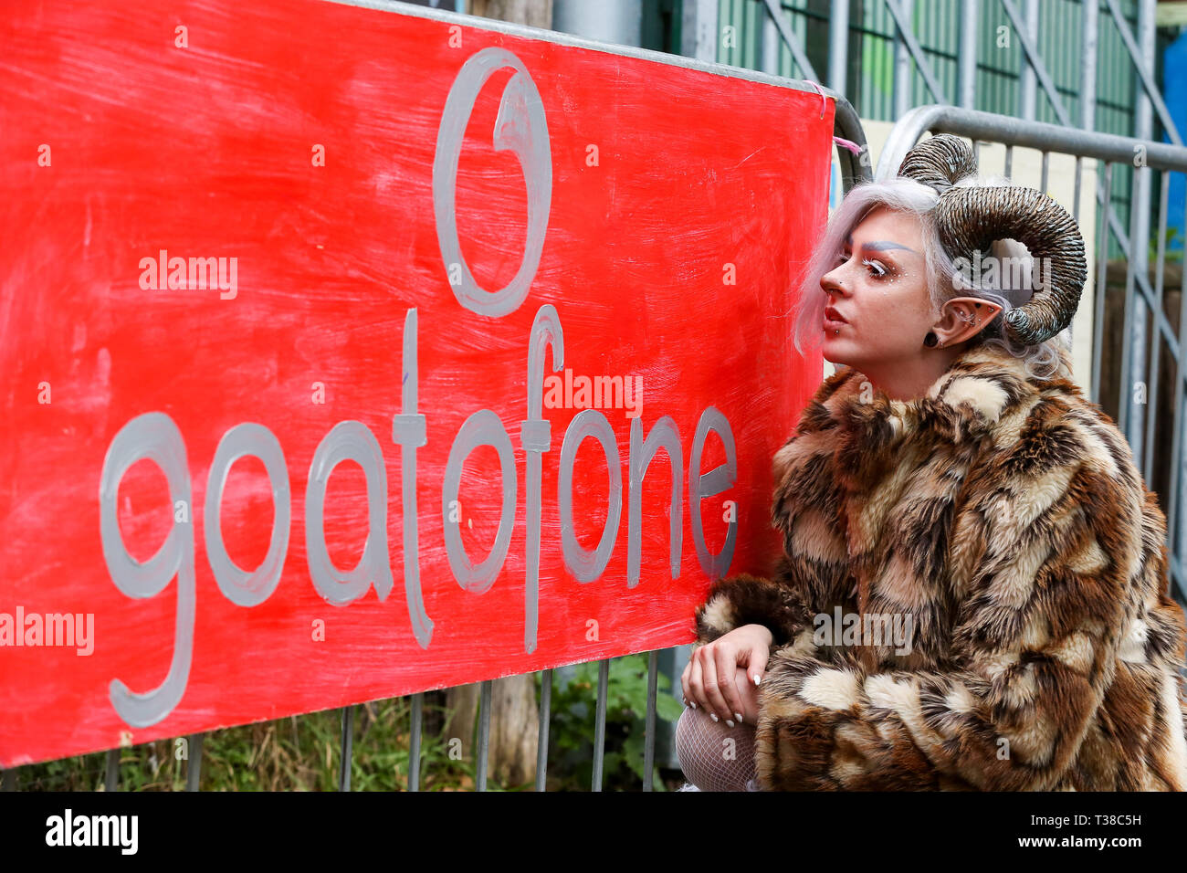 London, UK, UK. 7th Apr, 2019. A woman wearing goat horns is seen standing next to a banner before the Oxford vs Cambridge Goat Race in East London.Two pygmy goats compete during the 10th Oxford and Cambridge Goat Race at Spitalfields City Farm, Bethnal Green in East London. The annual fundraising event, which takes place at the same time as the Oxford and Cambridge boat race, where two goats, one named Hamish representing Oxford and the other Hugo representing Cambridge to be crowned King Billy. Credit: Dinendra Haria/SOPA Images/ZUMA Wire/Alamy Live News - Stock Image
