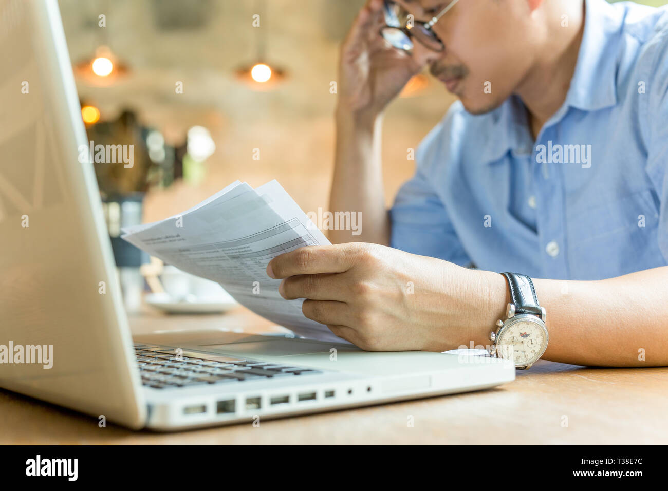 Worries businessman hands on his head looking at document with laptop on table. - Stock Image