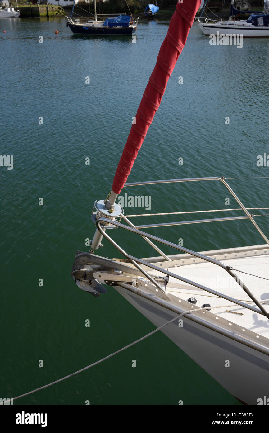 Bow of sailing boat with stainless steel guardrail and furled jib with red   uv protective cloth and two sailing boats in background in north wales uk - Stock Image