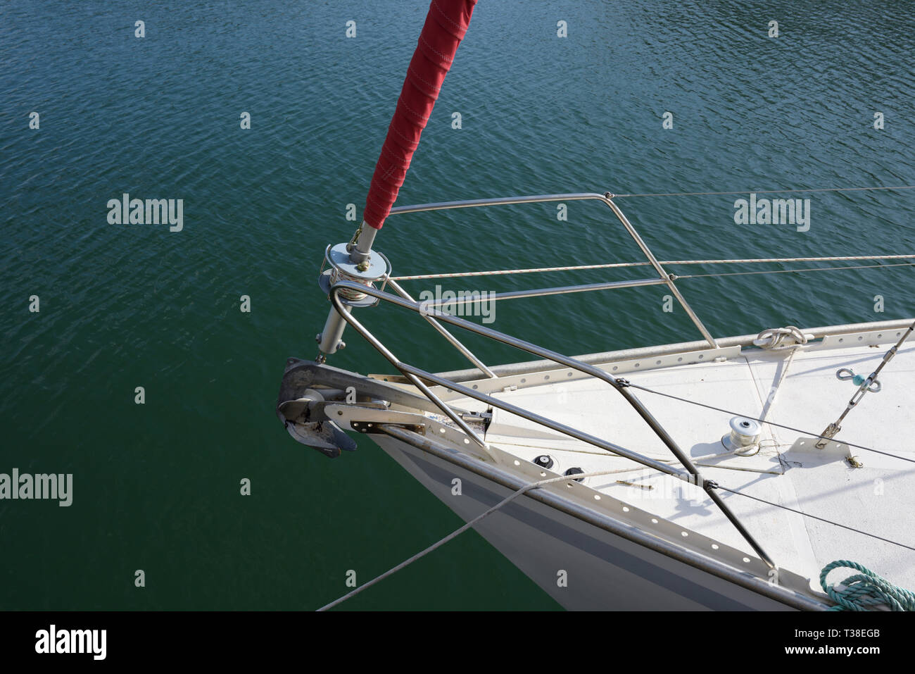 Bow of white sailing boat with stainless steel guardrail and furled jib with red uv protective cover, in north wales uk - Stock Image