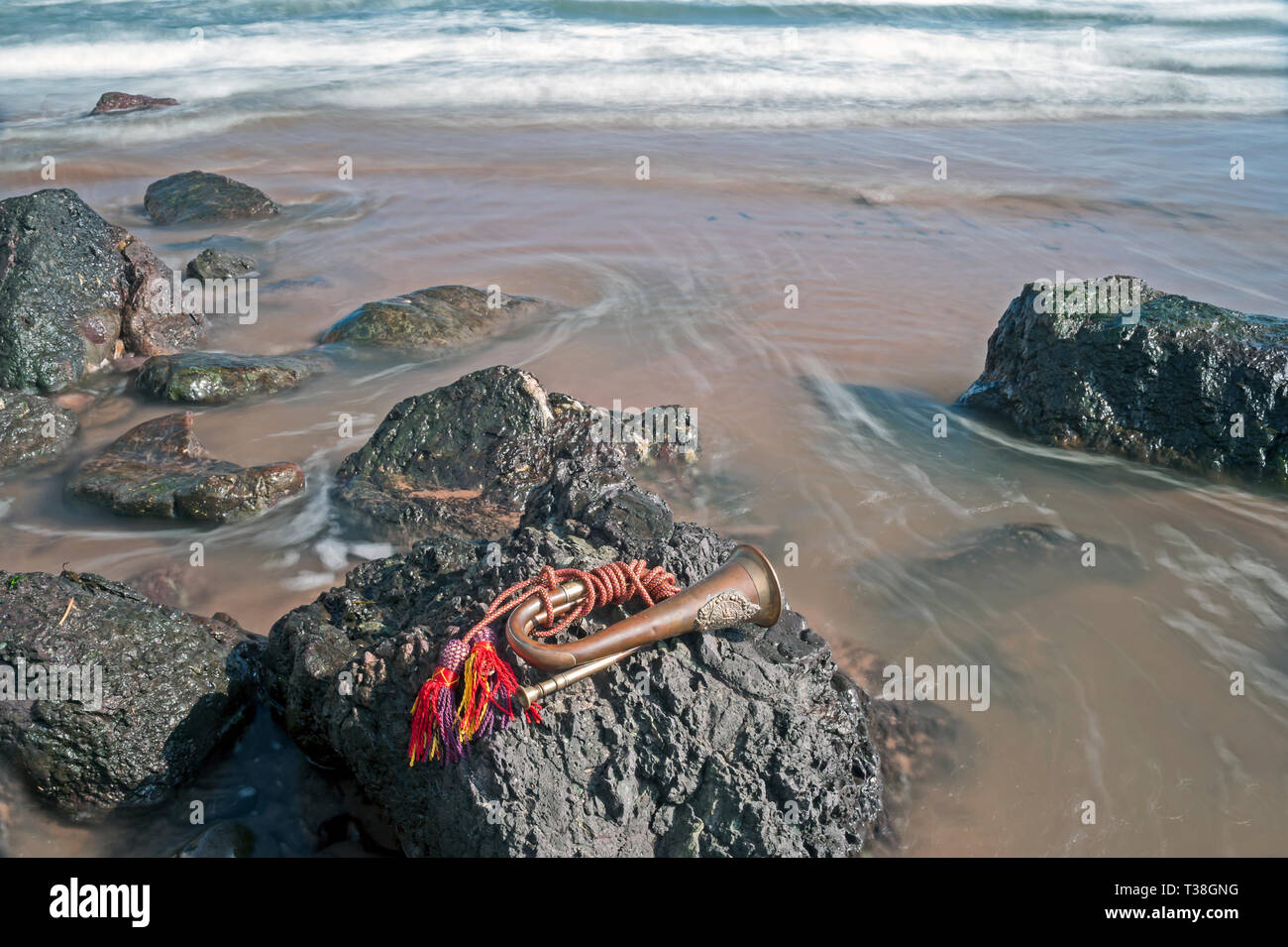 Concept  of patriotism, comradeship, remembrance and bravery with Argyll and Sutherland Highlander's bugle lying on rock at low tide at  low tide - Stock Image