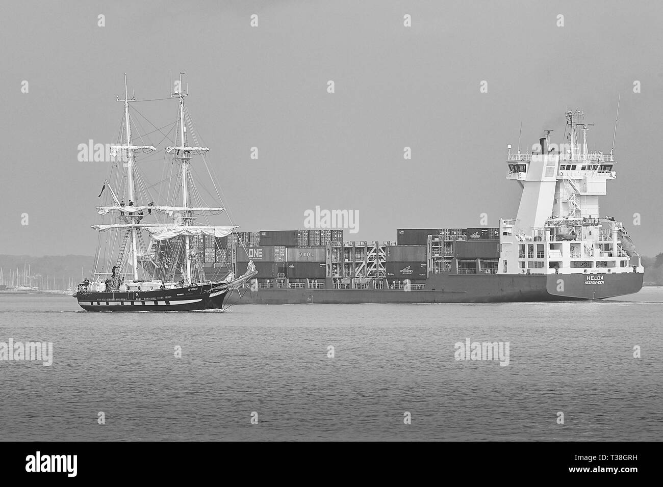 Black And White Photo Of The Training Ship, TS ROYALIST (Tall Ship), Departing The Port Of Southampton, Passes The Inbound Container Ship, HELGA. - Stock Image