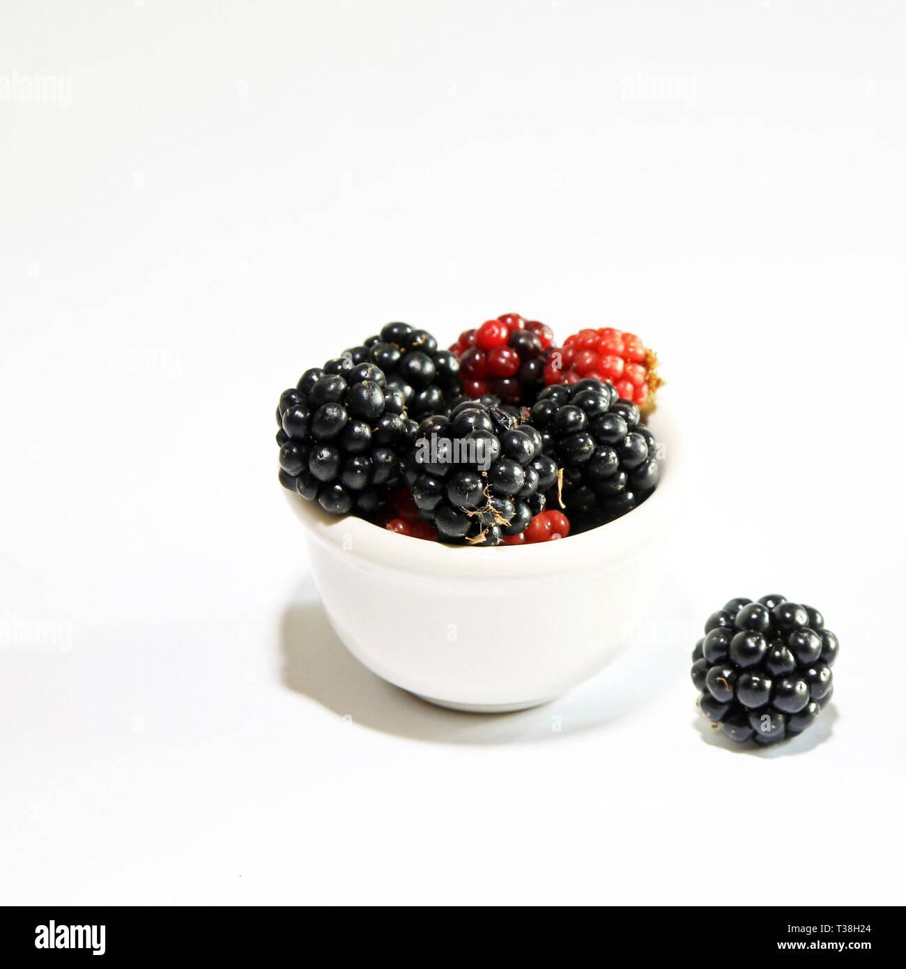 bowl of fresh blackberries on white background - Stock Image