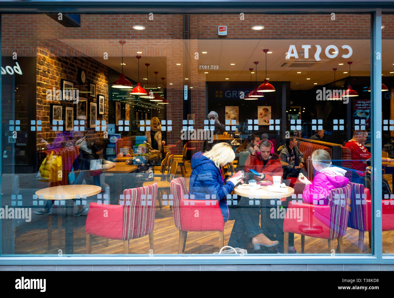Coffee Shop reflections looking into a Greggs coffee shop window with a reflection of a Costa shop opposite with customers enjoying their refreshments Stock Photo