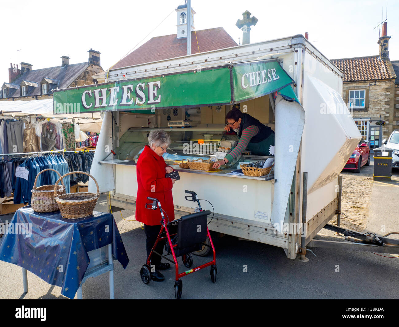 A woman buying Cheese from  a farmer's market stall in Helmsley  North Yorkshire England UK Stock Photo