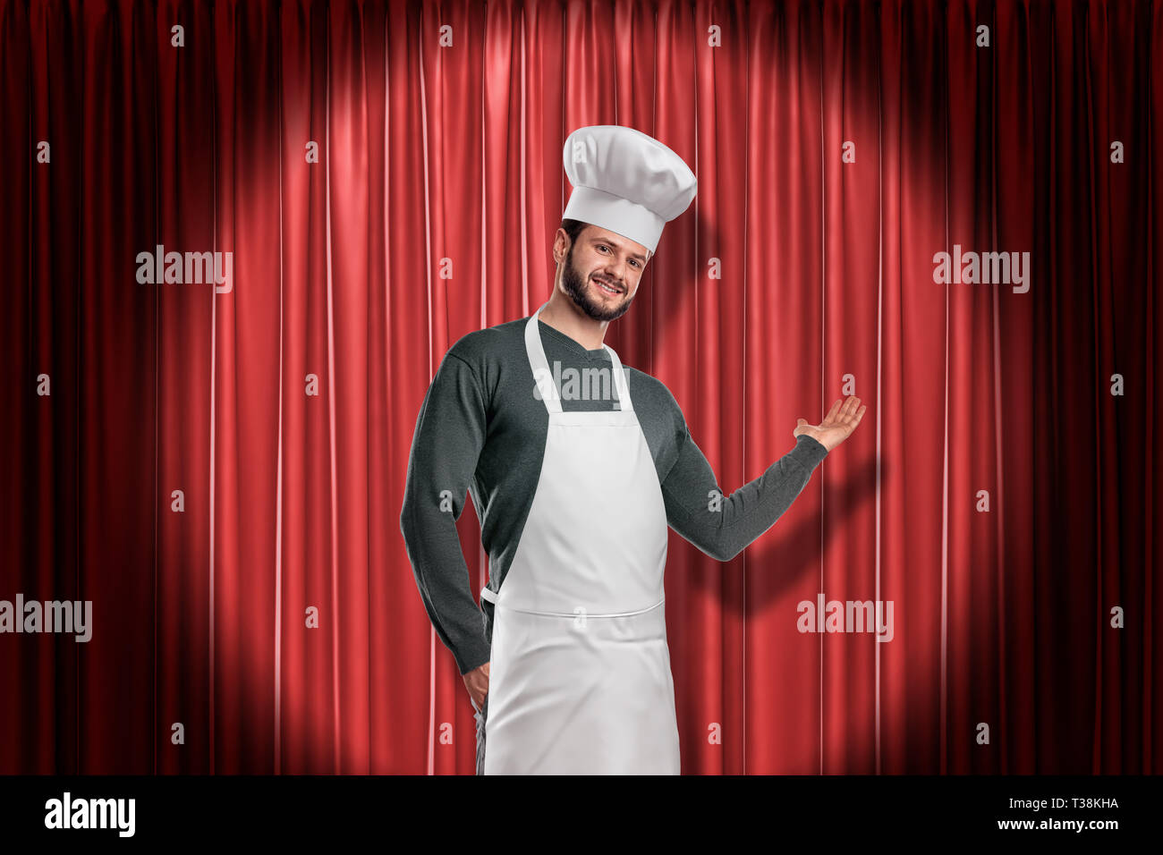 Young smiling handsome chef in white hat and apron lit up by limelight making presenting gesture at red stage curtain. - Stock Image