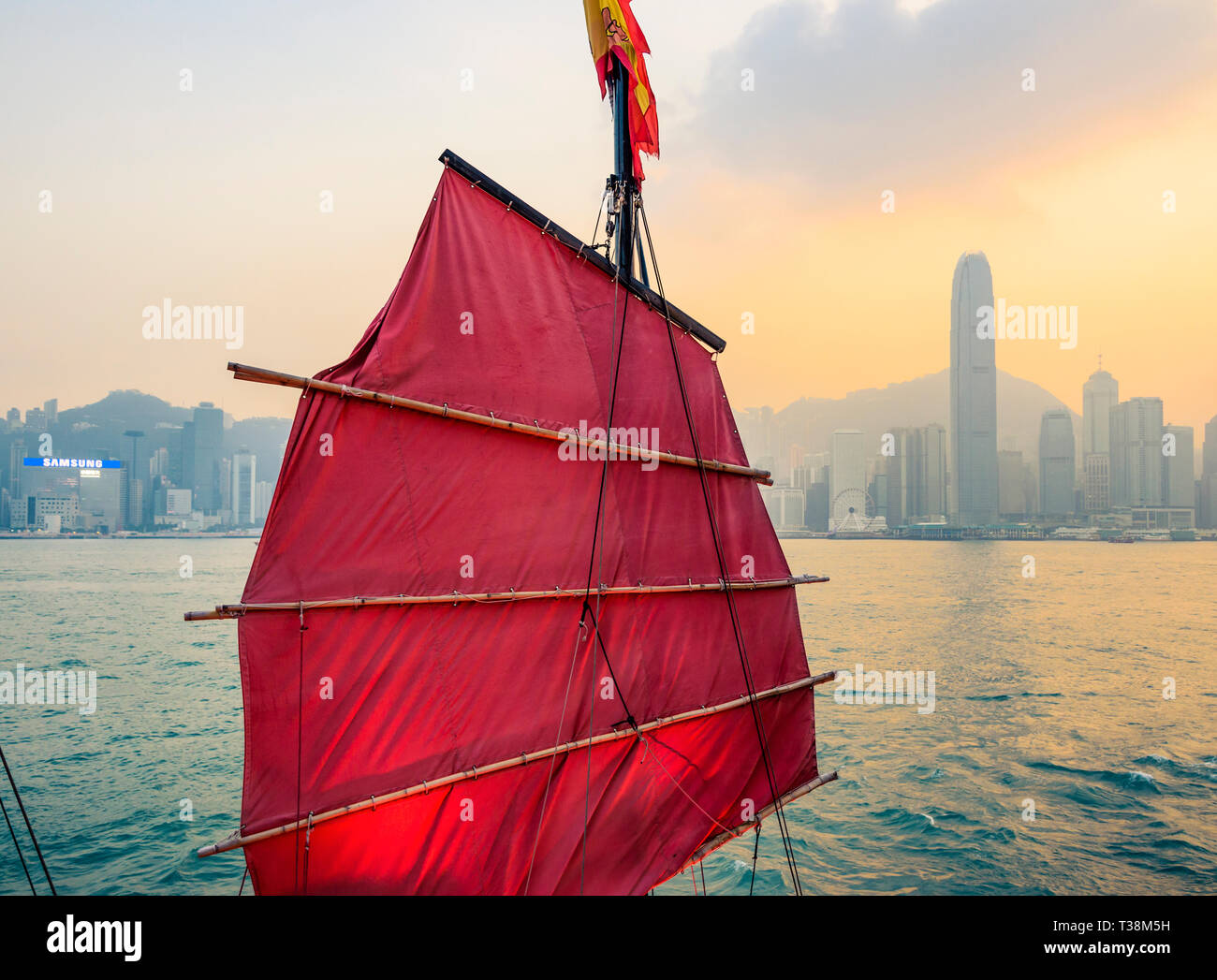 Sail detail of the Aqualuna junk tourist boat at sunset with the Hong Kong Island skyline behind, Victoria Harbour, Hong Kong - Stock Image