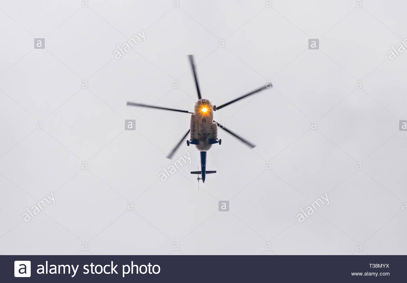 Silhouette of a big military transport helicopter seen from the ground against gray sky. Rotating propeller blades and  signal lights. - Stock Image