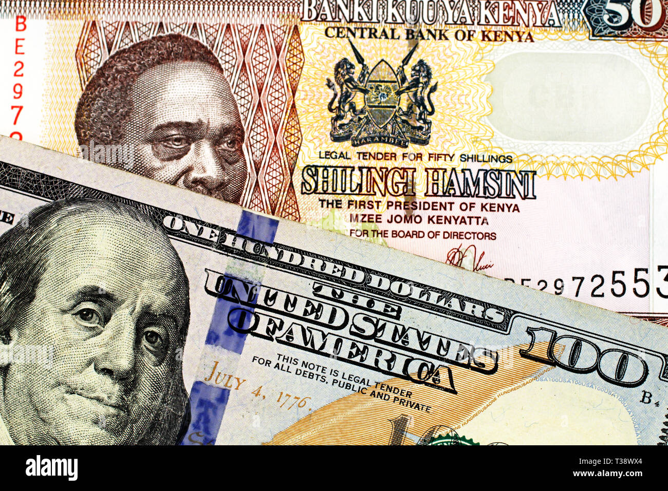 A close up image of a blue American one hundred dollar bill close up with a fifty Kenyan shilling bank note in macro Stock Photo