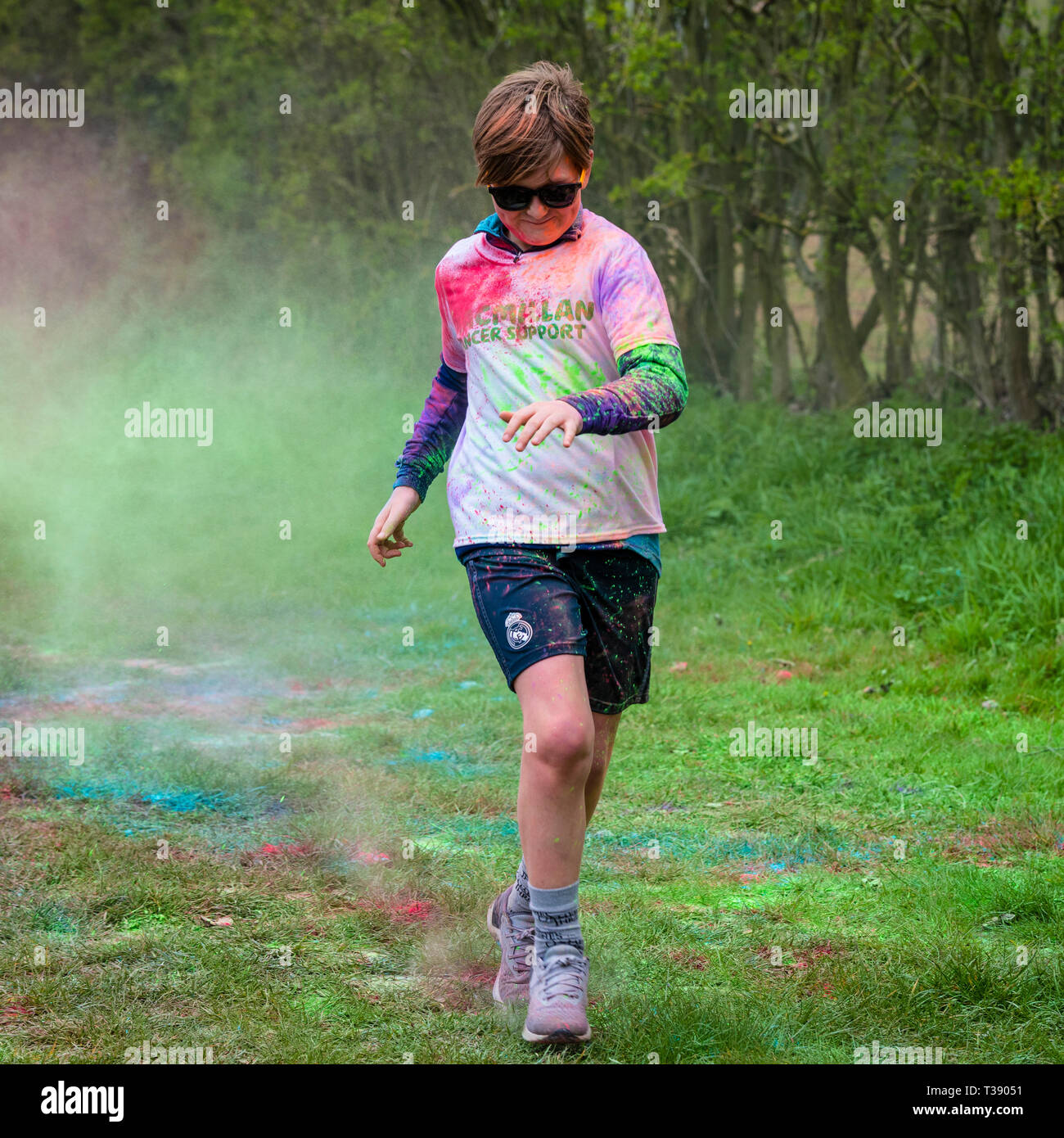 Young boy running hard and covered in paint on Macmillan cancer charity 5K colour fun run. - Stock Image