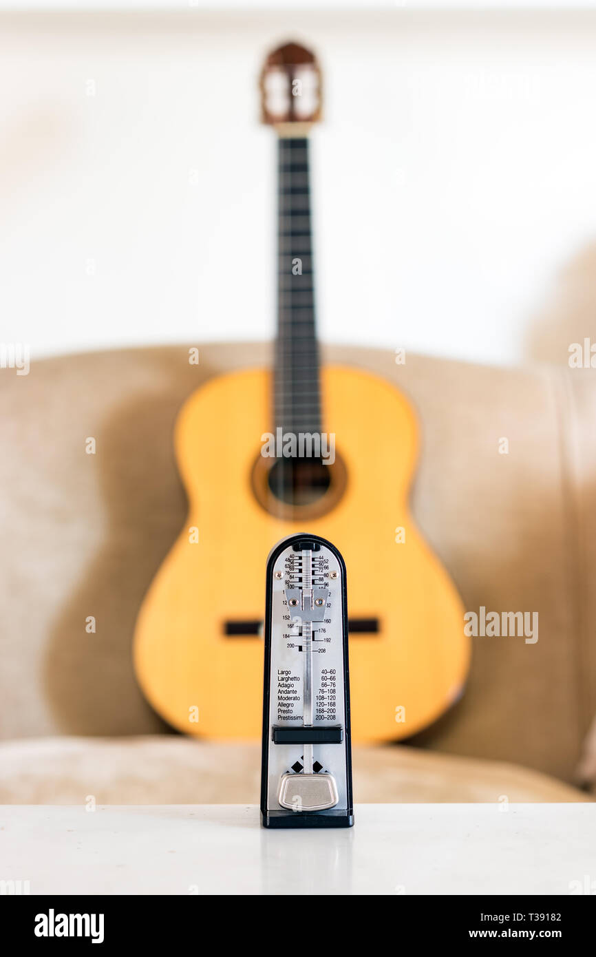 Mechanical metronome over a wooden classical acoustic guitar background. - Stock Image