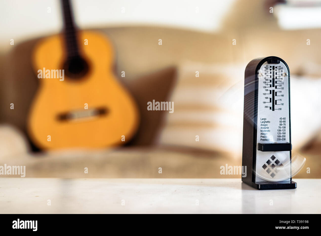 Mechanical metronome in motion, over a wooden classical acoustic guitar background. - Stock Image