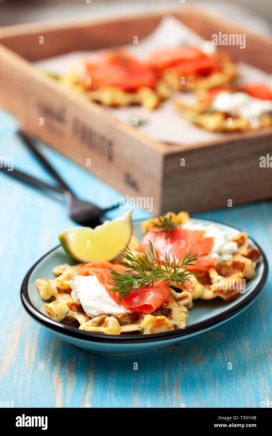 potato waffles with salmon, cream cheese on a blue wooden background. Stock Photo