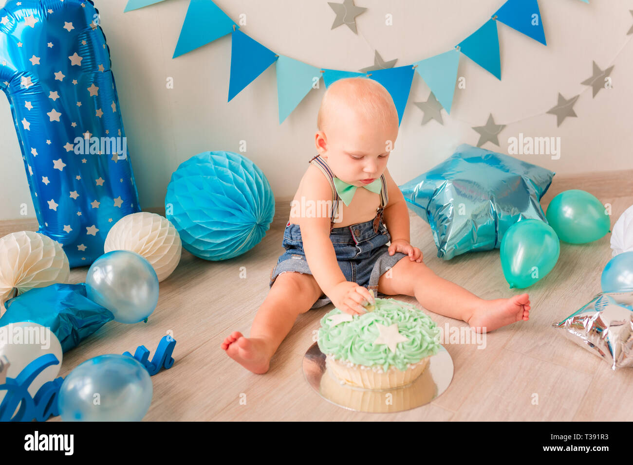 Adorable Baby Boy Celebrating His First Birthday Smash Cake Party