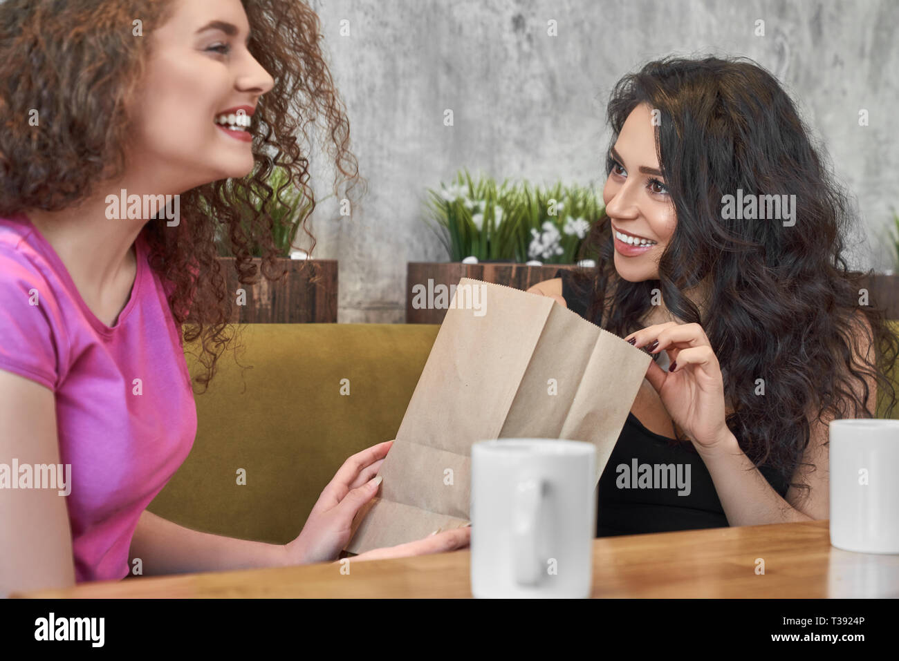Pretty Curly Woman Making Present To Best Female Friend In Cafe Happy Girl Showing Package With Gift For Birthday Sister And Laughing Cheerful Gi