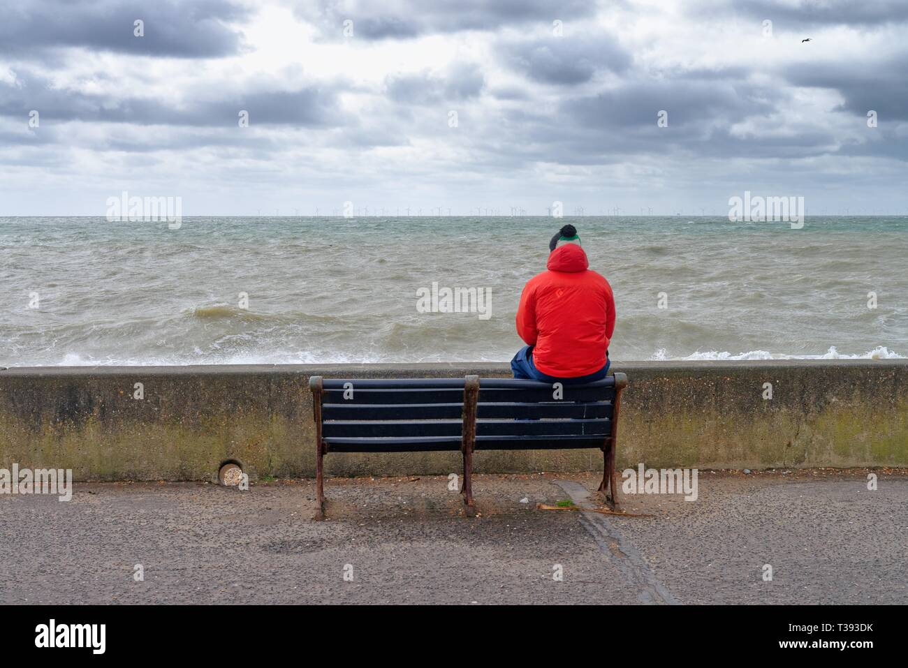 Male figure in red coat sitting on back of bench looking out to sea on the seafront at Hove east Sussex England UK - Stock Image